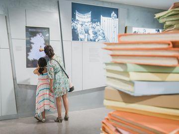 Im Vordergrund ist ein Teil einer Akteninstallation zu sehen. Im Hintergrund stehen eine Frau und ein mädchen an einer Medienstation und berühren den Bildschirm.