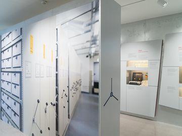 Das Bild zeigt eine Ausstellungswand, die einer Hebelschubanlage im Stasi-Unterlagen-Archiv nachempfunden wurde.
