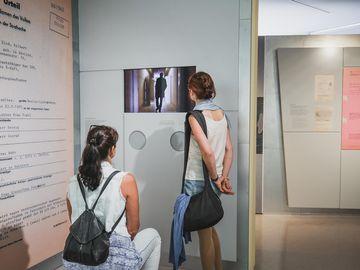 Zwei Frauen, die eine sitzend, die andere stehend, betrachten einen Monitor in der Ausstellung.