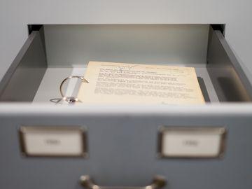 Eine bedruckte Aktenseite liegt in einer geöffneten Schublade.