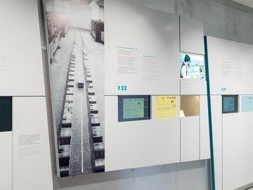 Das Bild zeigt eine Ausstellungswand, mit groflächigen Bilder, Text und Medienstationen zu den Thema Karteisystemen der Stasi.