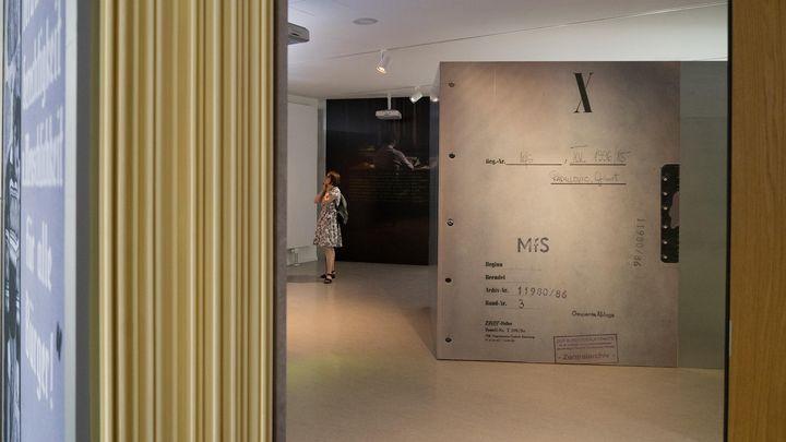 Blick in die begehbare Akte: Eine Frau schaut sich eine Ausstellungstafel an.