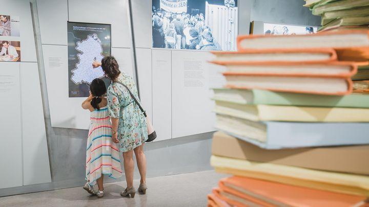 Zwei Besucherinnen, eine Erwachsene und ein Kind, informieren sich an einer Medienstation. Beide tragen sommerliche Kleidung.