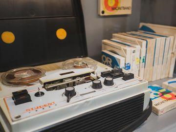 Das Bild zeigt ein Tonbandgerät und mehrere Tonbänder in Hüllen daneben.