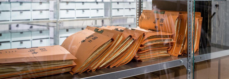 Das Bild zeigt im Vordergrund Akten in der Lagerung, wie die Stasi sie praktizierte. Im Hintergudn sind die Katen, wie heute im Stsai-Unterlagen-Archiv üblich, in Kartons verpackt.