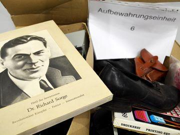 Auf dem Bild ist ein Karton mit verschiedenen Gegenständen zu sehen. Ein Foto von Richard Sorge, ein schwarzer Schuh und ein Stempelkasten.