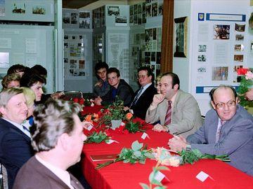 Auf dem Bild sieht man Stasi-Mitarbeiter an einer Festtafel. Im Hintergrund sind die Ausstellungstafeln des Traditionskabinetts zu sehen.