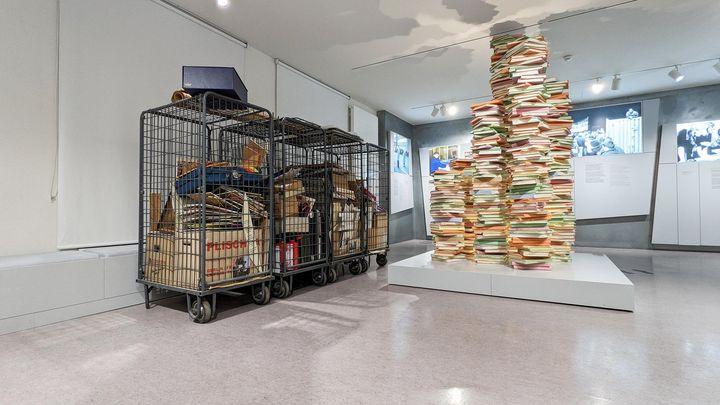 Auf dem Bild sieht man vier Gitterboxen. In ihnen befinden sich Kartons, Koffer und viele Tafeln. Daneben steht die Skulptur eines Aktenstapels in der Ausstellung.