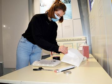 Auf dem Bild sieht man eine studentische Mitarbeiterin, die gerade ein Etikett auf einen verpackten Gegenstand klebt.