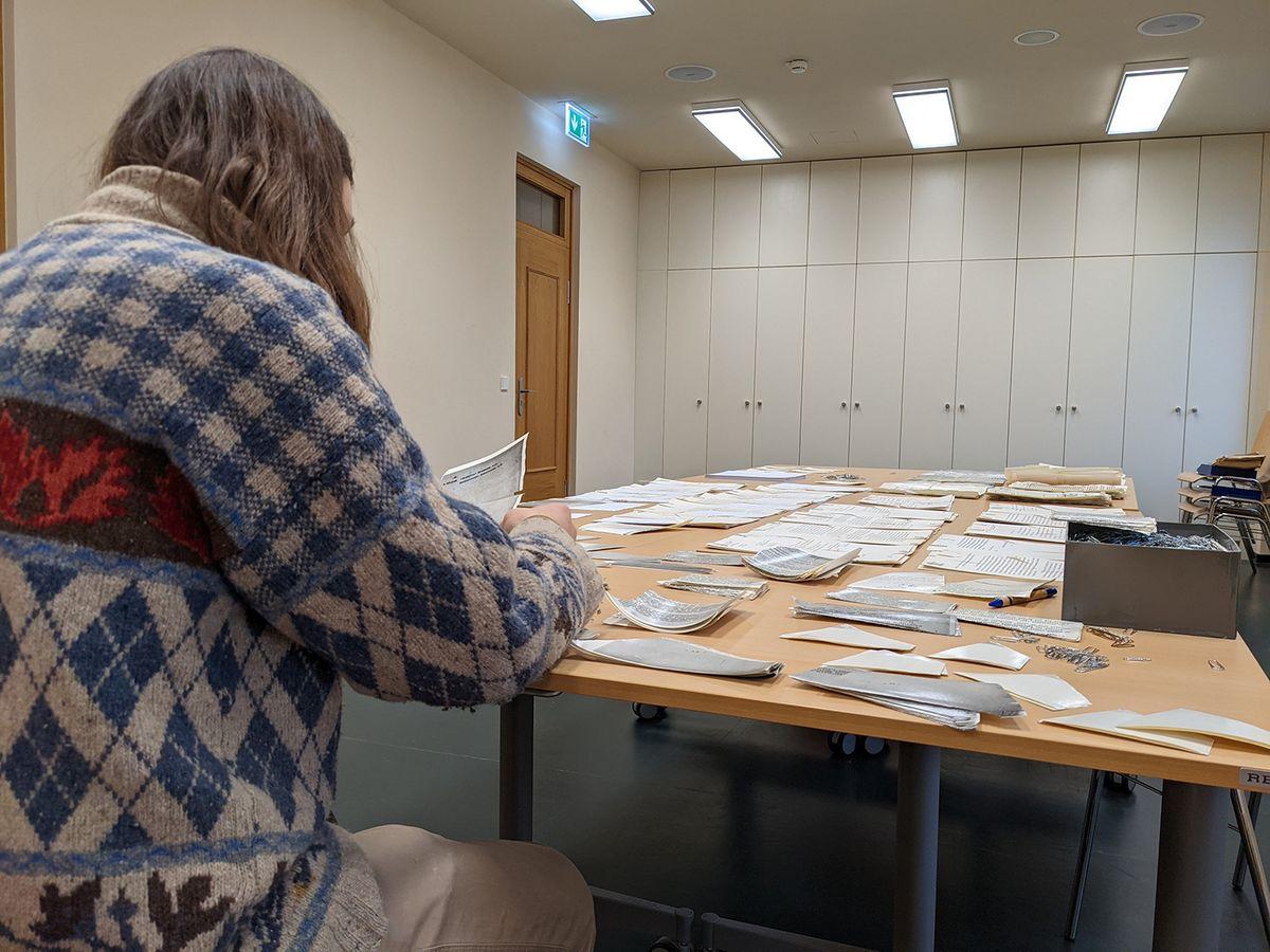 Das Bild zeigt einen Studenten, der an einem Tisch sitzt, der voller zerrissener Unterlagen ist. Im Hintergund ist eine Schrankwand und eine Tür zu sehen.