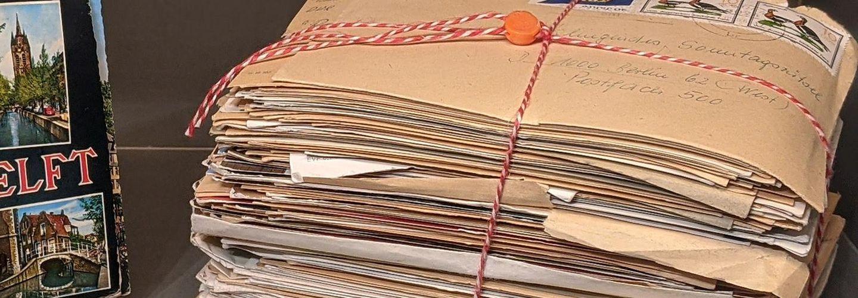 Das Bild zeigt eine Vitrine in der Ausstellung 'Einblick ins Geheime' mit einem Stapel durch die Stasi abgefangener und einbehaltener Briefe an die RIAS-Radiosendung 'Das klingende Sonntagsrätsel'.