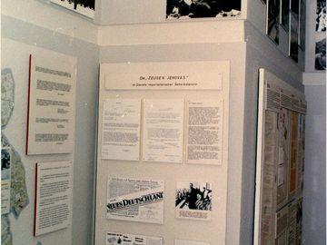 Auf dem Bild sieht man einige Ausstellungstafeln der Stasi über die Zeugen Jehovas. Darauf sind Zeitungsberichte und Dokumente zu sehen.