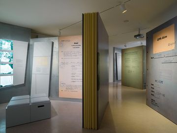 Das Bild zeigt einen Ausstellunsgraum mit mehrere überlebensgroßen Aktenseiten und -deckeln sowie zwei Medienstationen.