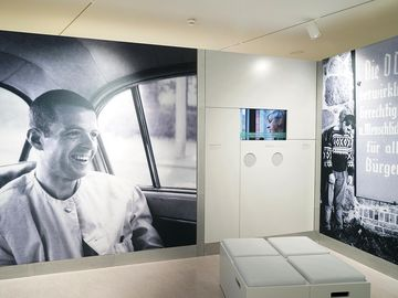 The picture shows two big pictures of Gilbert Radulovic and a screen showing an interview with Radulovic.