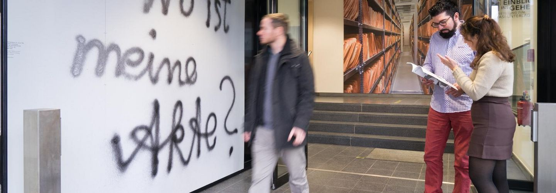 Das Bild zeigt Besuchende im Eingangsbereich der Ausstellung 'Einblick ins Geheime'. An einer Wand steht: 'Wo ist meine Akte?'