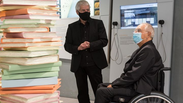 Das Bild zeigt Roland Jahn und Wolfgang Schäuble im Gespräch im Empfangsraum der Ausstellung. Im Vordergrund ist eine Aktenskulptur zu sehen, im Hintergrund einige Medienstationen.