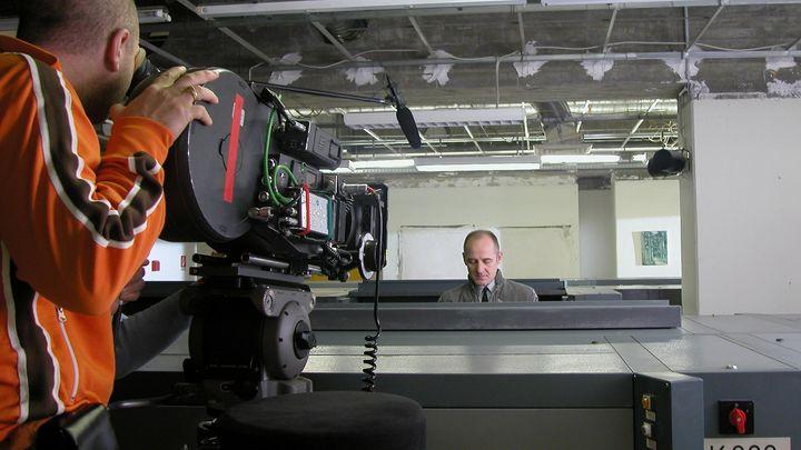 Das bIld zeigt eine Kamera, die auf einen Schauspieler gerichtet ist. Dieser sitzt an einem Schreibtisch und schaut leicht nach unten.