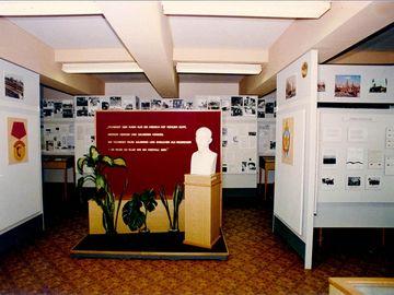 Auf dem Bild ist die Ausstellung der Hauptabteilung XX der Stasi zu sehen. In der Mitte eine Büste von Felix Dzierżyński vor einer Wand mit einem Titat. Rundherum sieht man Ausstellungstafeln.