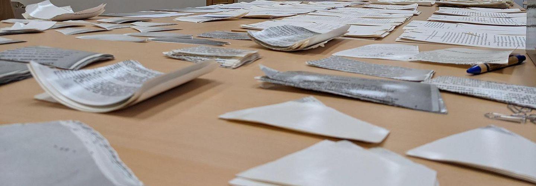 Auf dem Bild ist ein Tisch zu sehen, der fast vollkommen von Schnipseln zerrissener Unterlagen bedeckt ist. Im Hintergund sieht man eine Schrankwand und eine Tür.
