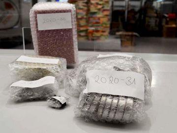 Auf dem Bild sieht man in Luftpolsterfolie verpackte Metallscheiben, so genannte Petschaften. Außerdem sieht man eine verpackte Box. Im Hintergrund ist die Ausstellung zu erkennen.
